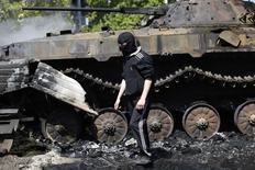 Человек в маске проходит мимо сгоревшего бронетранспортера в Мариуполе 10 мая 2014 года. Украинская армия понесла во вторник самые многочисленные потери с начала операции, призванной подавить вооружённых пророссийских сепаратистов: погибли 7 десантников, попавшие в засаду на востоке, сообщило Минобороны. REUTERS/Marko Djurica