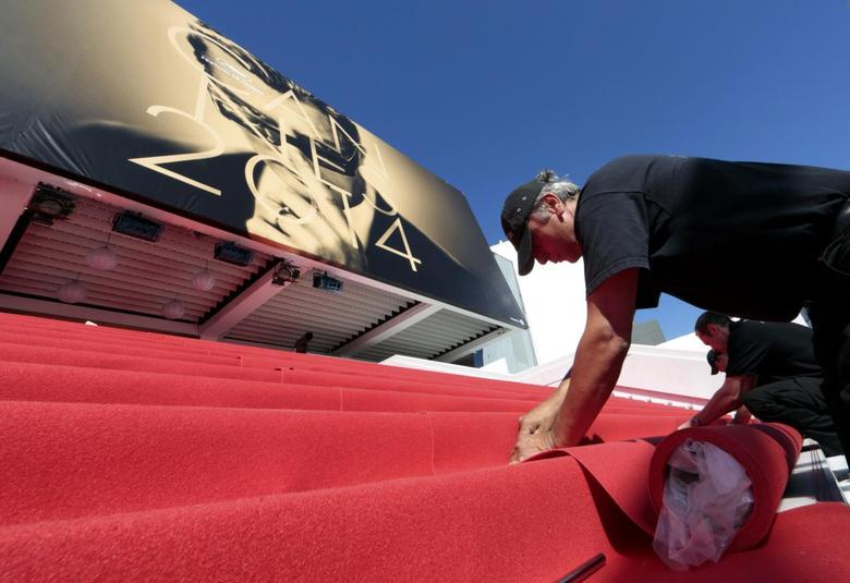 Workers install the red carpet in front of the main entrance of the Festival Palace for the opening ceremony of the 67th Cannes Film Festival in Cannes May 14, 2014.        REUTERS/Eric Gaillard