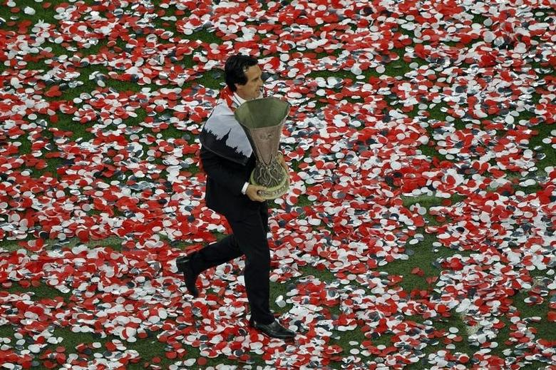 Sevilla's coach Unai Emeri holds the cup after his team defeated Benfica in their Europa League final soccer match at the Juventus stadium in Turin May 14, 2014.   REUTERS/Alessandro Garofalo