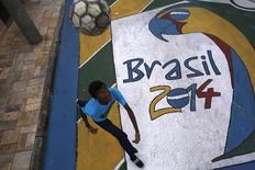 Lucas, de 15 anos, joga bola em uma rua decorada para a Copa do Mundo, em São Paulo, nesta semana. 14/05/2014 REUTERS/Nacho Doce