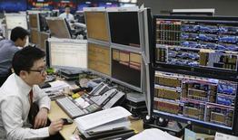 Валютные дилеры в торговом зале банка в Сеуле 4 апреля 2013 года. Азиатские фондовые рынки, кроме Южной Кореи, снизились в понедельник под влиянием валютных курсов и отдельных отраслей. REUTERS/Lee Jae-Won