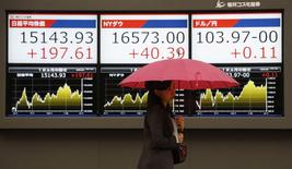 Женщина проходит мимо табло с котировками в Токио 3 апреля 2014 года. Азиатские фондовые рынки, кроме Южной Кореи, выросли во вторник за счет отдельных отраслей. REUTERS/Toru Hanai