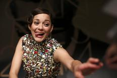 """Cast member Marion Cotillard reacts as she signs autographs at the end of a news conference for the film """"Deux jours, une nuit"""" (Two Days, One Night) in competition at the 67th Cannes Film Festival in Cannes May 20, 2014.          REUTERS/Benoit Tessier"""