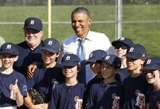 U.S. President Barack Obama poses with Little League baseball players and their coach at Friendship Park in Washington May 19, 2014. REUTERS/Yuri Gripas