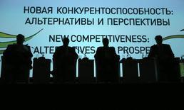 Участники экономического форума в Санкт-Петербурге, 22 мая 2014 года. Охлаждение отношений между Россией и Западом из-за Украины создало проблемы с привлечением внешнего финансирования, которое было существенным подспорьем для развития крупных компаний, признают российские банкиры и надеются выиграть от ситуации, заместив спрос на рыночные ресурсы кредитами. REUTERS/Sergei Karpukhin