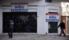 Pedestrian walk past a store that went out of business, now for rent, in Buenos Aires May 22, 2014. After a decade of growth, Argentina faces a sharp decline this year as industrial output falls and one of the world's highest inflation rates hits consumer spending and new investment. Picture taken May 22, 2014.       REUTERS/Marcos Brindicci (ARGENTINA - Tags: POLITICS BUSINESS)