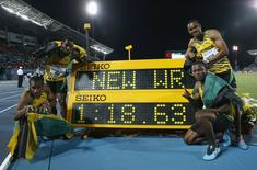 Jamaica's 4x200 relay team poses next to the clock after they set a new world record while winning the 4x200 metres relay at the IAAF World Relays Championships in Nassau, Bahamas, May 24, 2014. At left is Nickel Ashmeade (top), Yohan Blake (bottom) and at right is Warren Weir (top) and Jermaine Brown (bottom). REUTERS/Mike Segar