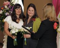 Julia Fraser (L) and Jessica Rohrbacher (C) recite wedding vows with Celebrant Holly Pruett (R) at the Melody Ballroom in Portland, Oregon May 19, 2014. REUTERS/Steve Dipaola