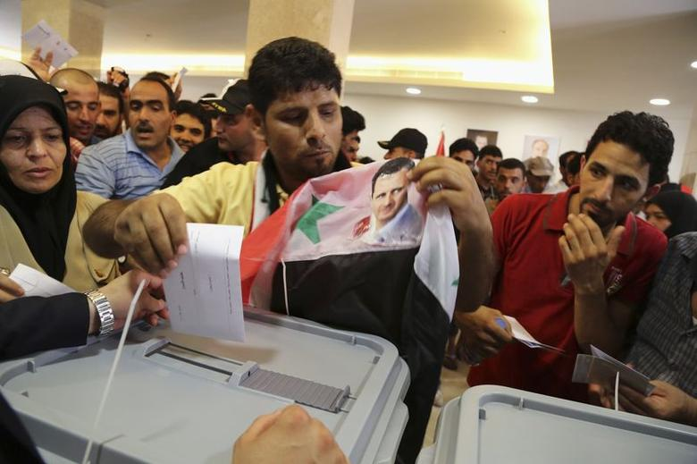 A Syrian national living in Beirut casts his vote ahead of the June 3 presidential election as he holds a Syrian national flag with Syria's President Bashar al-Assad's picture on it at the Syrian Embassy in Yarze, east of Beirut May 28, 2014. REUTERS/Sharif Karim