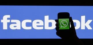 Ilustración fotográfica donde una mujer sostiene un teléfono móvil con el logo de Whatsapp detrás de un logo de Facebook en Praga, feb 20 2014. La red social Facebook pidió a los reguladores antimonopolio de la Unión Europea (UE) que examinen su adquisición del servicio de mensajería instantánea para móviles WhatsApp por 19.000 millones de dólares, dijo el miércoles una fuente con conocimiento directo del asunto.    REUTERS/David W Cern