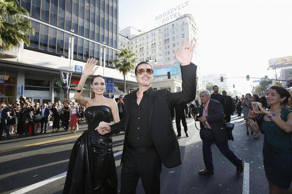 Cast member Angelina Jolie and actor Brad Pitt wave at fans as they arrive at the premiere of ''Maleficent'' at El Capitan theatre in Hollywood, California May 28, 2014.  REUTERS/Mario Anzuoni