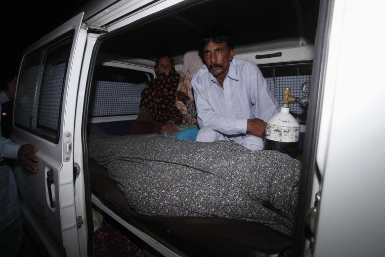 Mohammad Iqbal sits next to his wife Farzana's body, who was killed by family members, in an ambulance outside of a morgue in Lahore May 27, 2014. REUTERS/Mohsin Raza
