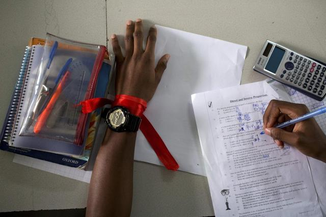 A student wears a red ribbon to express solidarity with the abducted Nigerian schoolgirls from the remote area of Chibok, as he does a maths exercise at the Regent Secondary School in Abuja, in this May 14, 2014 file photo. REUTERS/Joe Penney/Files