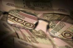 Рублёвые купюры в Москве 17 февраля 2014 года. Рубль упал в пятницу на фоне сужения предложения экспортной выручки после уплаты налогов и продолжавшегося с начала недели рыночного перепозиционирования после существенного майского укрепления российской валюты. REUTERS/Maxim Shemetov