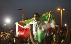 A Gaza, après la victoire de l'équipe de football palestinienne qui a remporté vendredi l'Asia Challenge Cup en battant les Philippines 1-0 aux Maldives. Ce sacre - le premier dans une compétition internationale-,  lui permet de se qualifier pour la Coupe d'Asie des nations qui sera disputée en janvier prochain en Australie. /Photo prise le 30 mai 2014/REUTERS/Mohammed Salem
