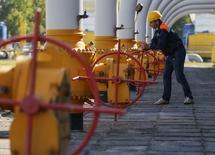 Рабочий крутит вентиль на территории газового хранилища в городе Стрый 21 мая 2014 года. Газпром отодвинул угрозу перебоев экспорта газа в Европу - получив часть денег от задолжавшей миллиарды долларов Украины, российский экспортер на неделю отодвинул старт режима предоплаты и согласился обсудить снижение цены. REUTERS/Gleb Garanich