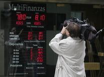 Un camarógrafo firma una pantalla que desplega el tipo de cambio del peso argentino con otras monedas, en Buenos Aires, 24 de enero del 2014. Las monedas latinoamericanas seguirían firmes esta semana a la espera de que el Banco Central Europeo (BCE) confirme el jueves las expectativas de los mercados globales, con el anuncio de un alivio monetario para evitar el peligro de la deflación en la zona euro. REUTERS/Enrique Marcarian