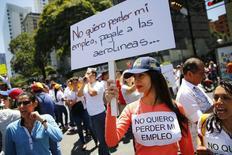 """Una trabajadora de una agencia de viajes participa en una protesta, en frente del edificio del Ministerio de Turismo en Caracas, en demanda de que el Gobierno de Venezuela pague a las aerolíneas, 23 de mayo del 2014. Venezuela está siendo """"tozudamente irresponsable"""" en su trato a las aerolíneas, que tienen más de 4.000 millones de dólares en ingresos atrapados en el país, dijo el martes un importante grupo de la industria. REUTERS/Jorge Silva"""