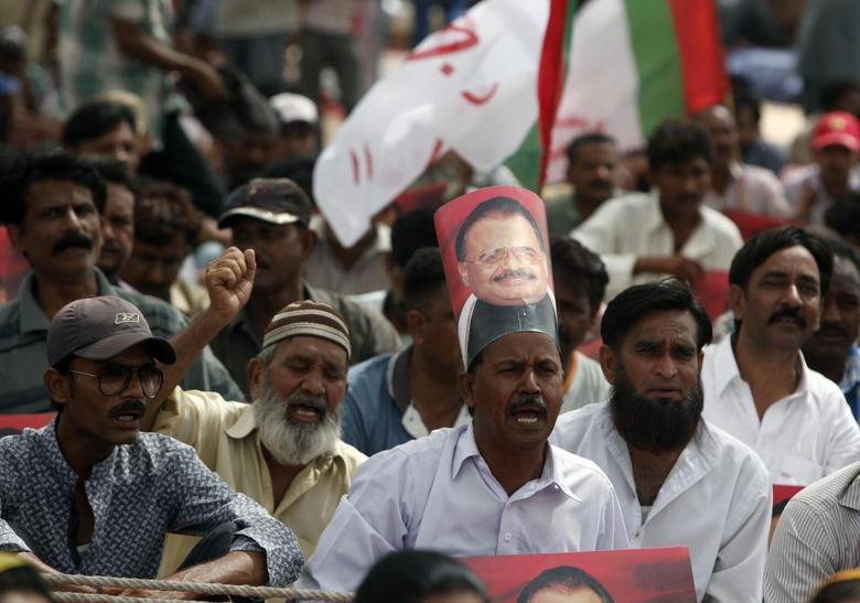 A supporter of Pakistan's Muttahida Quami Movement (MQM) political party, adorned a poster of Altaf Hussain on his head as he chants slogans along with others, to show solidarity with their leader in Karachi June 4, 2014. REUTERS/Akhtar Soomro