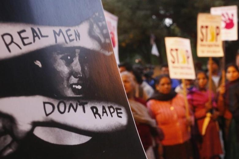 Demonstrators hold placards during a candlelight vigil to mark the first death anniversary of the Delhi gang rape victim in New Delhi December 29, 2013. REUTERS/Anindito Mukherjee/Files
