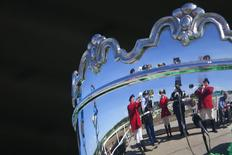 "Buglers are reflected in a trophy as they play the ""Call to Post"" before the 146th running of the Belmont Stakes in Elmont, New York June 7, 2014. REUTERS/Carlo Allegri"