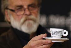 Sarajevo-born artist Dean Jokanovic Toumin, designer of a special edition illy coffee cup, holds up one of the cups, in the ARS AEVI museum of contemporary art in Sarajevo, June 4, 2014. REUTERS/Dado Ruvic