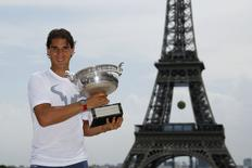 Rafael Nadal of Spain poses with his trophy for photographers near the Eiffel Tower, a day after winning his men's singles final match at the French Open tennis tournament at the Roland Garros stadium, in Paris June 9, 2014.  REUTERS/Gonzalo Fuentes