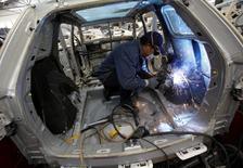 En la imagen un trabajador suelda un auto para ser arreglado en un garage en Ciudad de México, 15 de diciembre de 2010. La producción de vehículos de México subió un 12.5 por ciento en mayo a tasa interanual, mientras que las exportaciones crecieron un 22.7 por ciento, ambas a niveles máximos históricos, dijo el lunes la Asociación Mexicana de la Industria Automotriz (AMIA). REUTERS/Claudia Daut