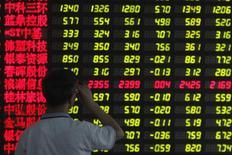 Инвестор в брокерской конторе в Шанхае 25 июня 2013 года. Возобновление работы рынка IPO материкового Китая, отмеченное семью новыми регистрациями на бирже во вторник, - это хорошая новость для инвесторов, хотя аналитики говорят, что брокеры, возможно, будут вынуждены сокращать прогнозы прибылей после четырехмесячной приостановки деятельности.  REUTERS/Aly Song