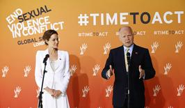 Actress and special envoy of the UN High Commissioner for Refugees (UNHCR), Angelina Jolie, watches as British Foreign Secretary William Hague speaks at a global summit to end sexual violence in conflict, in London June 10, 2014. REUTERS/Andrew Winning