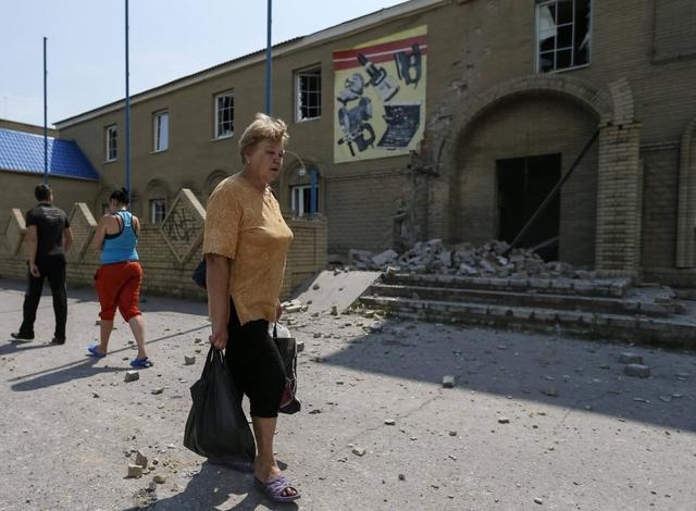 A woman cries as she passes destroyed houses following what locals say was overnight shelling by Ukrainian forces, in the eastern Ukrainian town of Slaviansk June 9, 2014.  REUTERS/Gleb Garanich