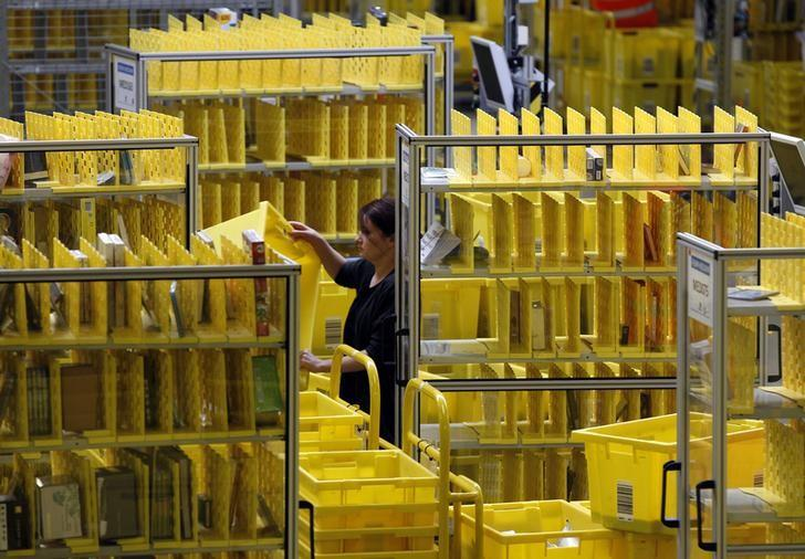 Worker collects items at Amazon's logistics centre in Graben near Augsburg December 16, 2013 file photo. REUTERS/Michaela Rehle