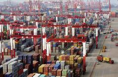 Camiones conducen a través de una pila de contenedores en el puerto de Qingdao, 8 de junio de 2014. China prometió a sus exportadores un conjunto de medidas cambiarias y crediticias que incluyen préstamos más baratos y otras herramientas, para reducir los riesgos de la tasa de cambio y ayudarlos a enfrentar una baja de las ventas. REUTERS/China Stringer Network
