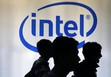En la imagen, unos jóvenes pasan junto a un logo de Intel durante una exposición en Yakarta, el 5 de marzo de 2014. El fabricante estadounidense de chips informáticos Intel perdió el jueves un recurso judicial contra una multa de 1.060 millones de euros impuesta por los reguladores antimonopolio de la UE hace cinco años por bloquear al rival Advanced Micro Devices (AMD). REUTERS/Beawiharta/Files