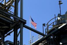 Una bandera de Estados Unidos en un mástil de una unidad de MDI 3 en la platan de poliuterano en Geismar, en Luisiana, 5 de mayo de 2014.  Las acciones de Estados Unidos caían el jueves tras una serie de datos económicos decepcionantes de consumo y mercado laboral, pero las acciones de energéticas subían con fuerza por un incremento de los precios del petróleo. USA-GERMANY/POWER REUTERS/Jonathan Bachman