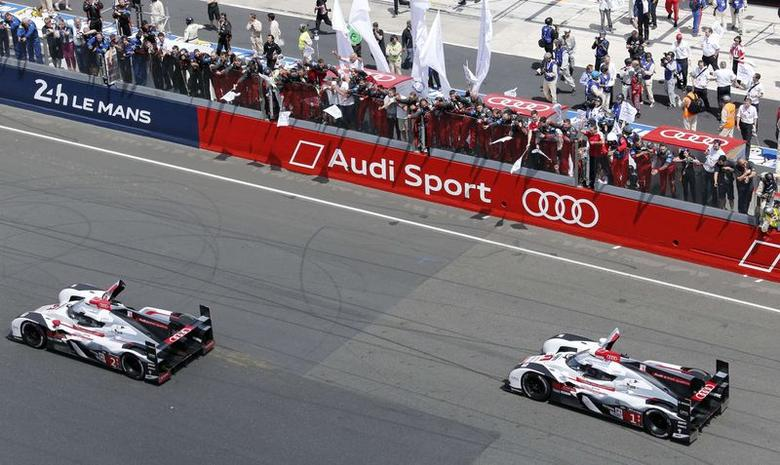 Audi team mechanics celebrate in the stands after France's Benoit Treluyer driving his Audi R18 e-tron Quattro number 2 crossed the finish line to win the Le Mans 24-hour sportscar race in Le Mans central France, June 15, 2014.  REUTERS/Regis Duvignau