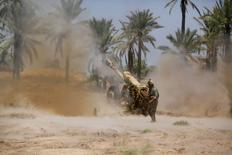 En la imagen, fuerzas de seguridad iraquíes disparan artillería durante los combates con el grupo de militantes suníes del Estado Islámico de Irak y el Levante en Jurf al-Sakhar el 14 de junio de 2014. Con la posibilidad de una escalada de la violencia en Irak, las acciones del sector de defensa podrían ganar mayor atención la próxima semana en la bolsa de Nueva York. REUTERS/Alaa Al-Marjani