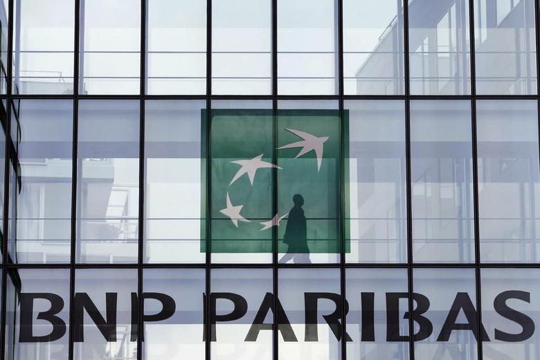 An employee walks behind the logo of BNP Paribas in a company's building in Issy-les-Moulineaux, near Paris, June 2, 2014. France is wary of speaking out about a U.S. criminal probe into BNP Paribas putting bilateral ties ahead of a threatened $10 billion-plus fine for its biggest listed bank, lawmakers indicated on Monday.   REUTERS/Charles Platiau (FRANCE - Tags: BUSINESS LOGO) - RTR3RVEQ