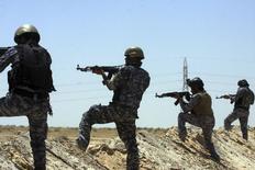 Иракские солдаты патрулируют район у границ провинций Кербела и Анбар 16 июня 2014 года. Президент Барак Обама обсудил в понедельник варианты военных действий для поддержки осажденного правительства Ирака, однако так и не вынес решения о реакции США на наступление суннитов, грозящее разорвать страну на части. REUTERS/Mushtaq Muhammed