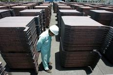 Un trabajador observa pilas de cobre en PT Smelting en Gresik, Indonesia, en la provincia del este de Java, 19 de marzo de 2008. El cobre subía el martes, debido a que la confirmación de las metas de crecimiento económico y las expectativas de nuevas medidas de estímulo en China calmaban a los inversores, al tiempo que las preocupaciones por una indagación sobre fraude en el financiamiento de metales en almacenes chinos se desvanecían. REUTERS/Sigit Pamungkas