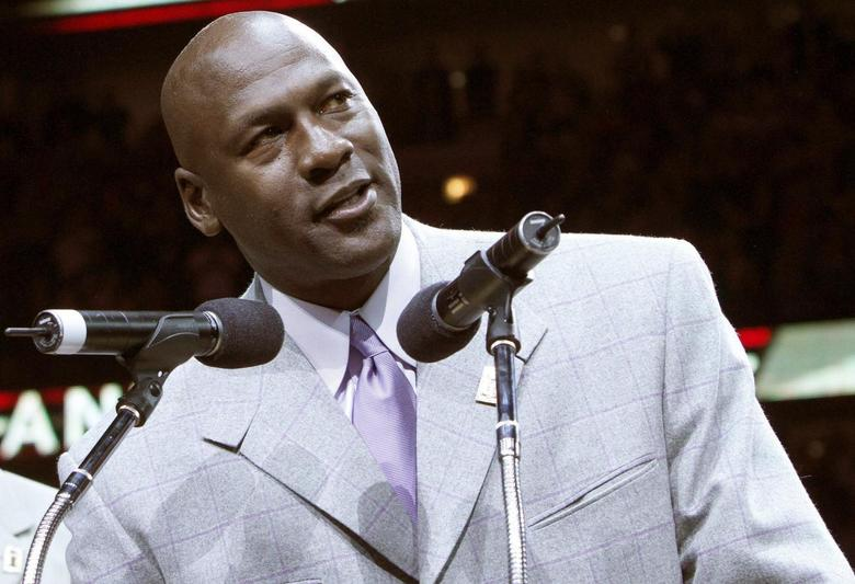 Former Bulls star Michael Jordan (R) talks to the crowd during a ceremony to honor the 20th anniversary of the Chicago Bulls' first world championship at half time of the NBA basketball game between the Utah Jazz and Chicago Bulls in Chicago, Illinois in this file photo from March 12, 2011.  REUTERS/Frank Polich/Files