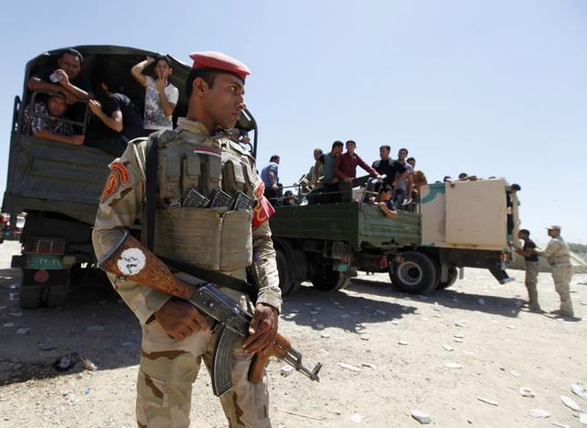 6月18日、イラク北部の都市バイジで、スンニ派武装組織が同国最大の製油施設を迫撃砲やマシンガンで攻撃した。写真手前はイラク治安部隊のメンバー。バグダッドで17日撮影(2014年 ロイター/Ahmed Saad)