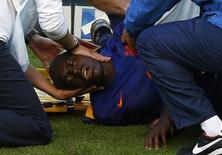 Holandês Martins Indi é retirado de campo após pancada na cabeça. REUTERS/Marko Djurica