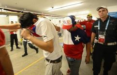 Torcedores chilenos são escoltados pela polícia depois de invadir centro de mídia para tentar ver o jogo contra a Espanha no Maracanã. 18/6/2014.   REUTERS/Dylan Martinez