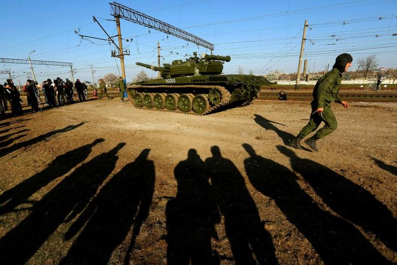 A Russian tank crew member runs in front of his T-72B tank after their arrival in Crimea in the settlement of Gvardeiskoye near the Crimean city of Simferopol March 31, 2014. REUTERS/Yannis Behrakis