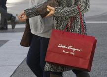 A shopper carries her purchases from the Salvatore Ferragamo boutique on Rodeo Drive, ahead of the Christmas festive season in Beverly Hills December 9, 2013. REUTERS/Fred Prouser