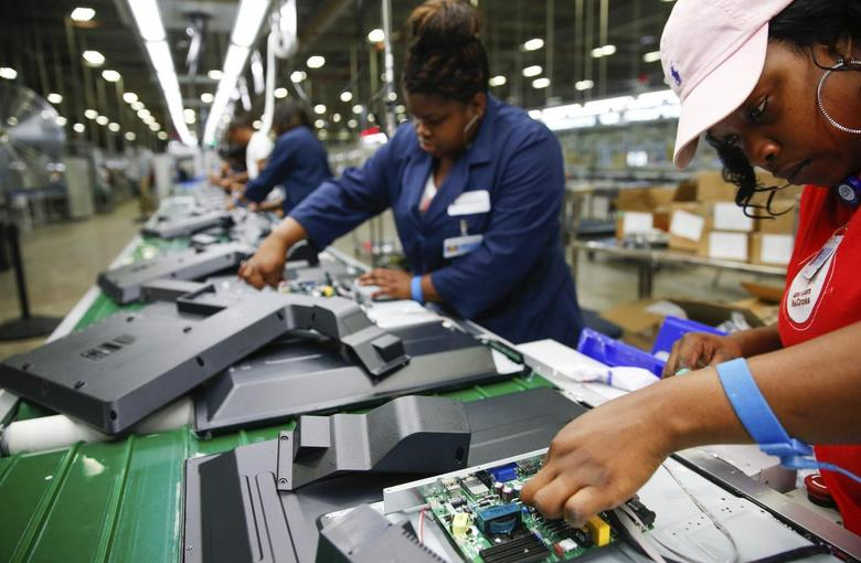 Workers on the assembly line work on installing the motherboard on the reverse side of a 32-inch TV at Element Electronics in Winnsboro, South Carolina May 29, 2014.  REUTERS/Chris Keane