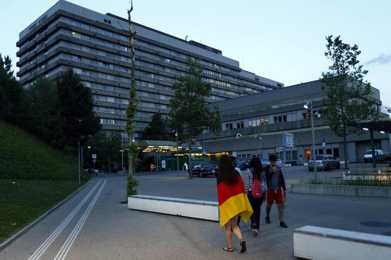 A woman draped with a German flag arrives at the University Hospital of Lausanne (CHUV) in Lausanne June 16, 2014.  REUTERS/Denis Balibouse