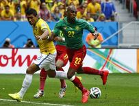 Cameroon's Allan Nyom (R) and Brazil's Paulinho (L) fight for the ball during their 2014 World Cup Group A soccer match at the Brasilia national stadium in Brasilia June 23, 2014. REUTERS/Michael Dalder (BRAZIL - Tags: SOCCER SPORT WORLD CUP)