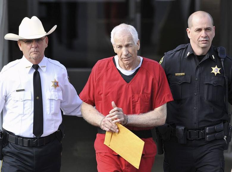 Jerry Sandusky (C) leaves the Centre County Courthouse after his sentencing in his child sex abuse case in Bellefonte, Pennsylvania in this file photo from October 9, 2012. REUTERS/Pat Little/Files
